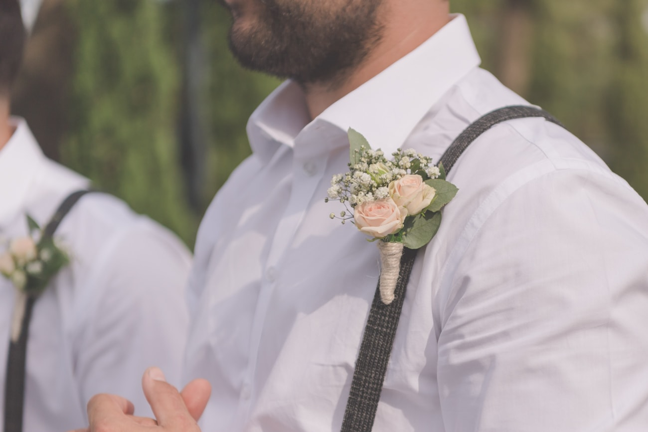 A groomsman's boutonnière with pale apricot roses