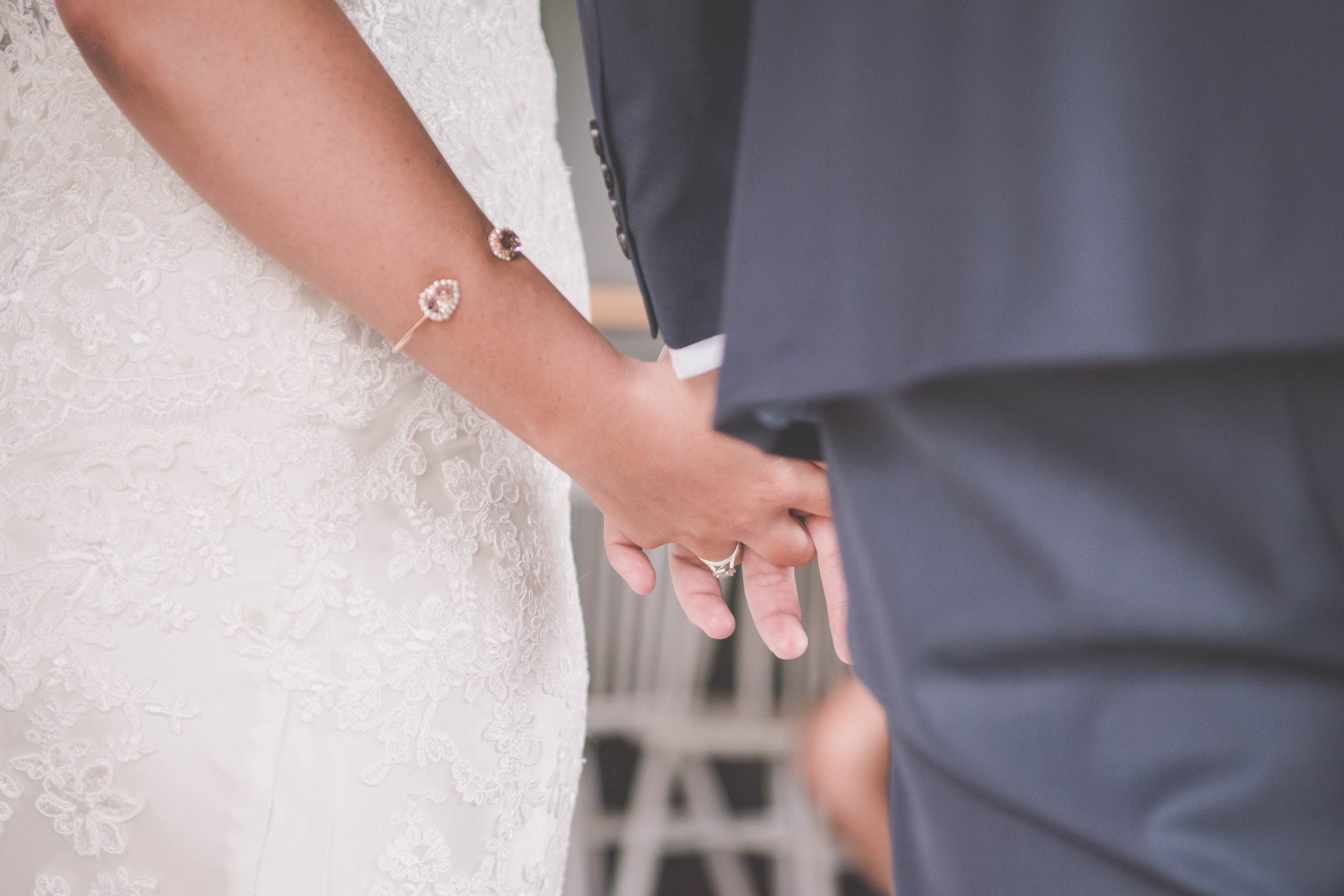 A bride and groom hold hands at their wedding
