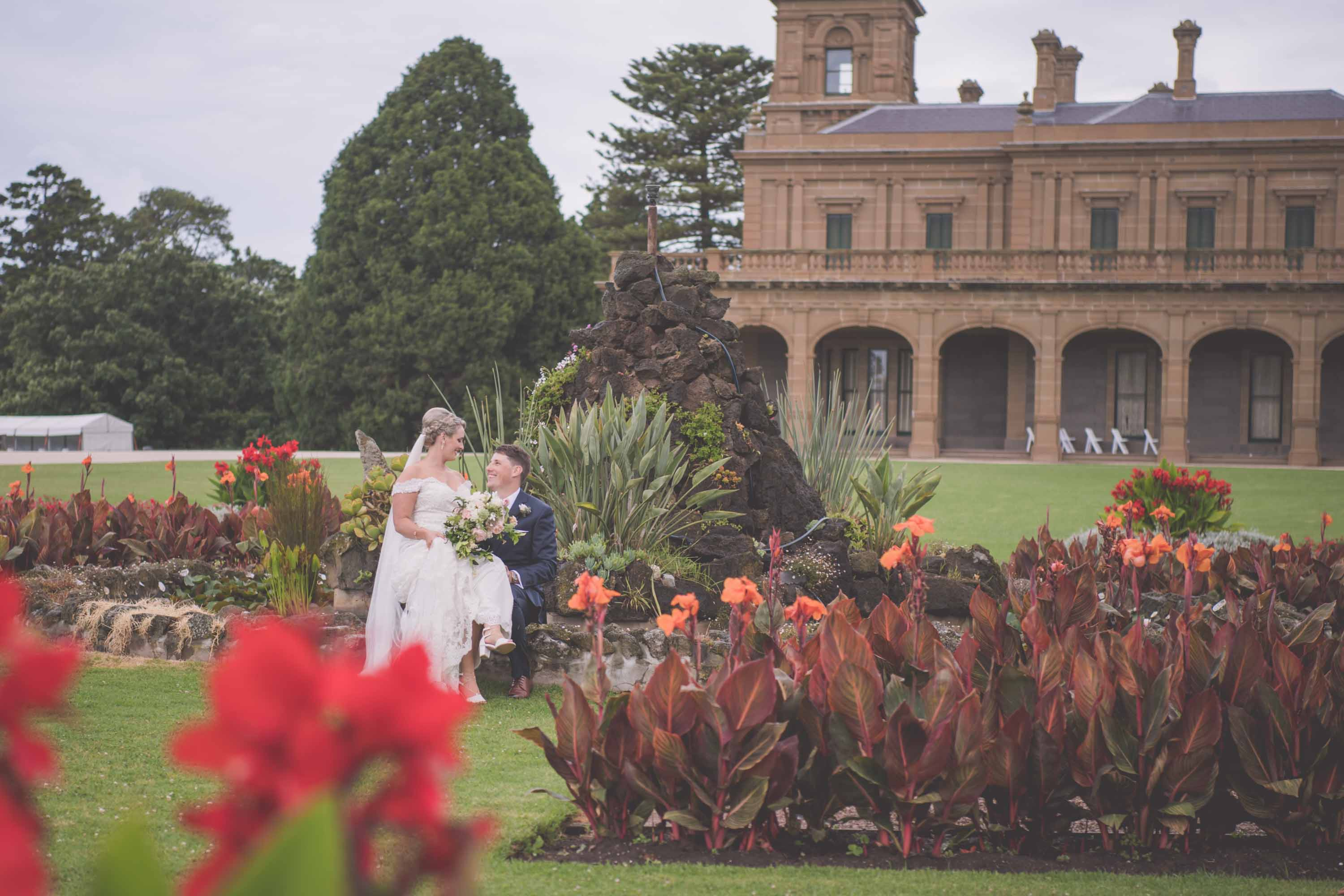 A couple sit for wedding photos at Werribee Mansion in Melbourne