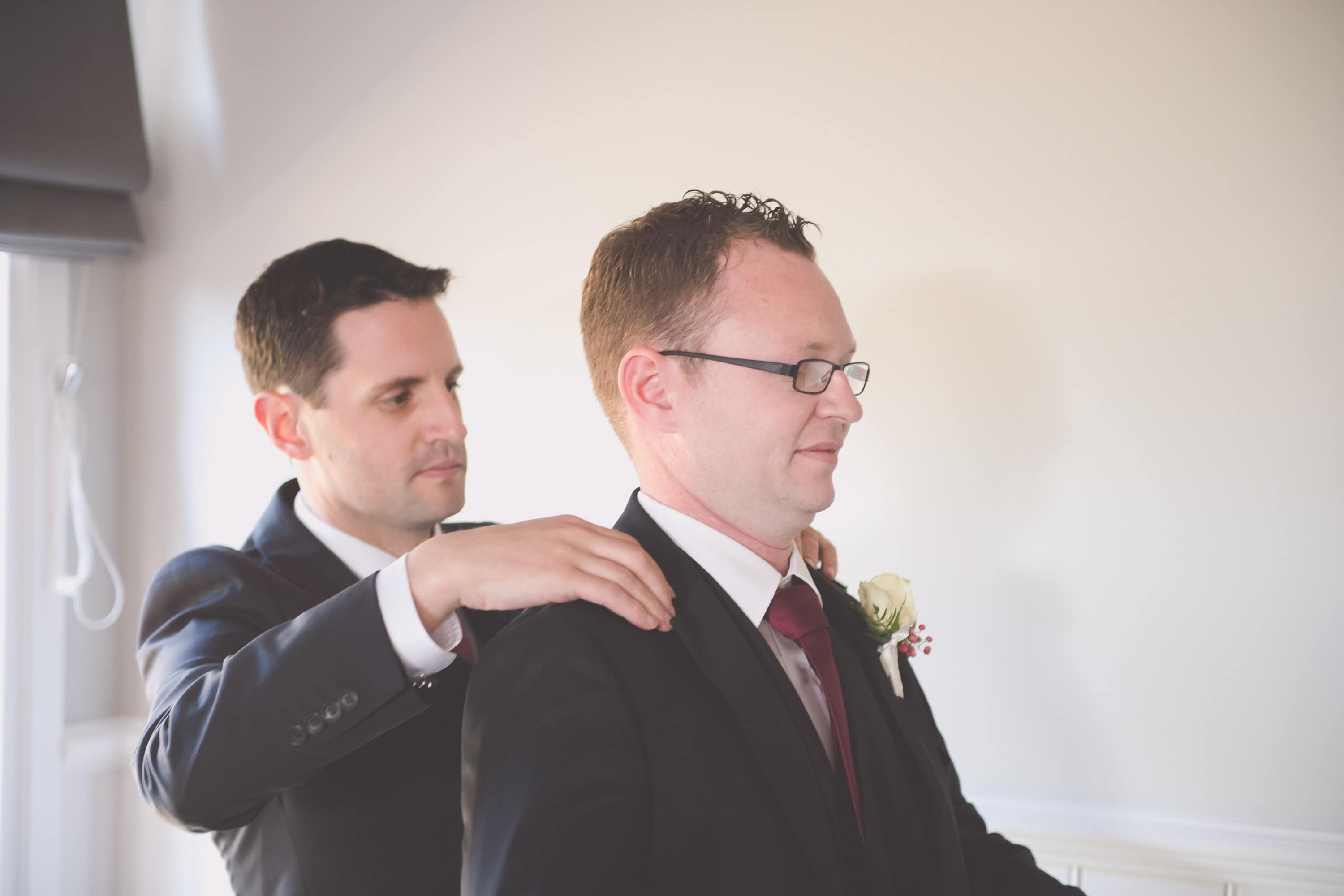 A best man helps his groom into his jacket