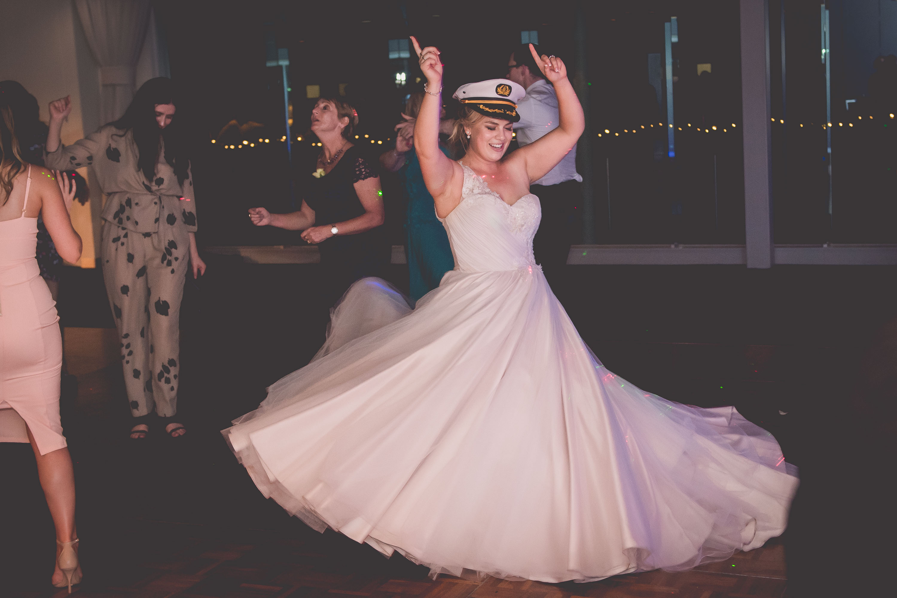 A bride wearing a captain's hat dances on her wedding dance floor
